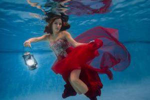 artistic underwater portrait of lady in a red dress underwater with lamp
